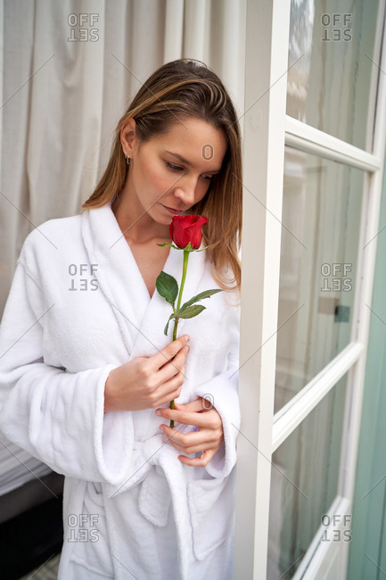 Thoughtful woman in white gown with fresh red rose smiling and dreaming while standing and looking down near windows at home
