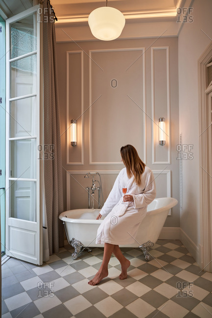 Charming playful female in white bathrobe with wineglass drink sitting on edge of bathtub while lounging in light spacious bathroom in vintage style