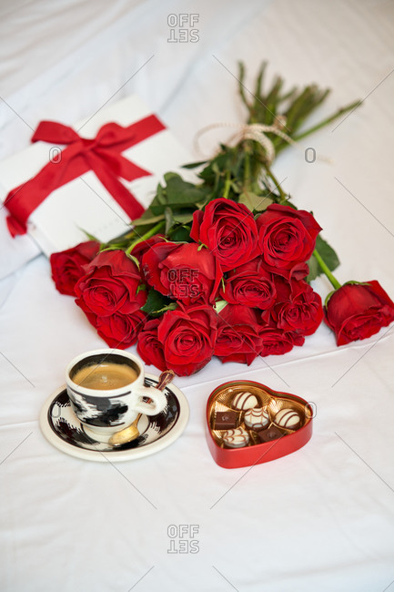 High angle of cup of hot drink and small heart shape box of candies in composition with bouquet of aromatic red roses on white bed