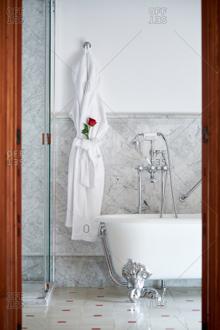 White bathrobe with fresh red rose in pocket hanging on hook among interior of clean light wet room with retro bath and open walk in shower in modern apartment