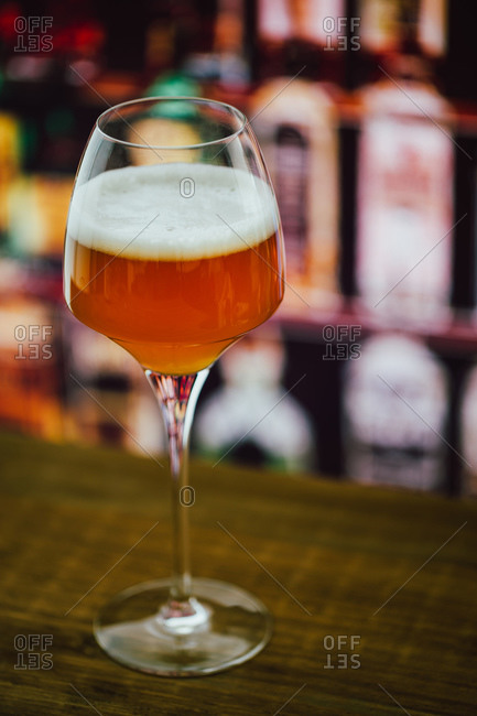 Beer in wineglass with foam in glass on wooden counter in bar on blur background