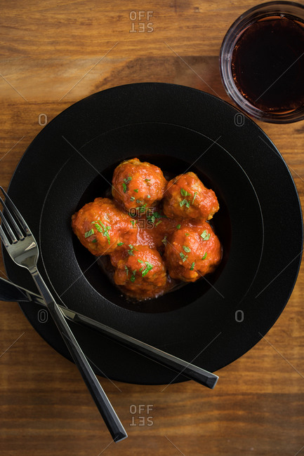 From above tasty cooked meatballs with tomato sauce serving with bread on black plate with cutlery and beverage on table