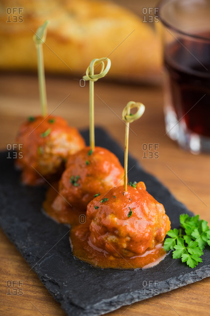 Tasty meat balls with tomato sauce bonded with bamboo sticks on flat board on table