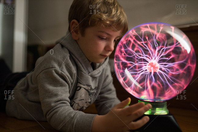 Side view of pensive child concentrating on looking at round lamp with pink neon streams at table