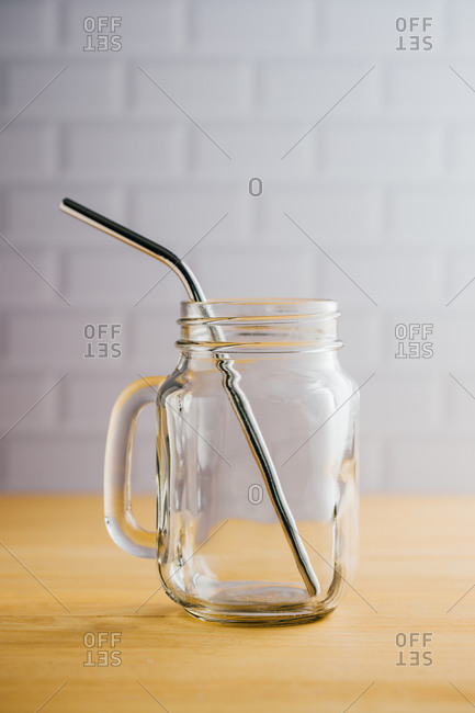 Several shiny steel straws in empty glass jug with handle on wooden table