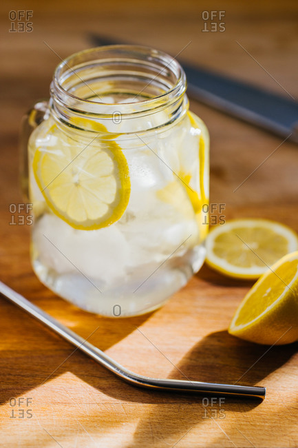 From above metallic reusable straw and glass jug with ice and lemon slices on wooden table in kitchen