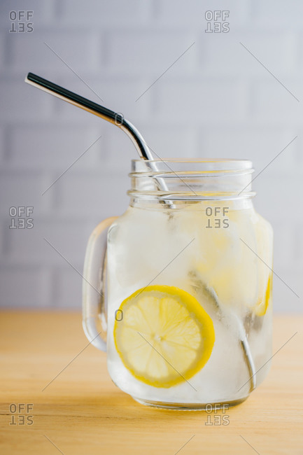 Metallic reusable straw and glass jug with ice and lemon slices on wooden table in kitchen