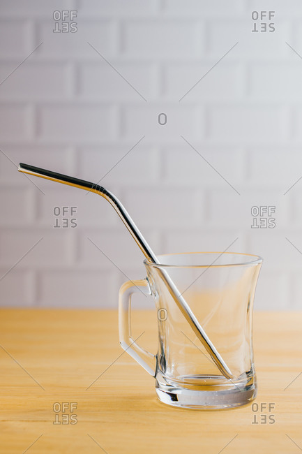 Shiny steel eco friendly sustainable straw in empty glass on wooden table