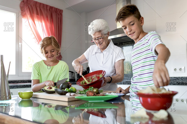Cheerful old woman with white hair helping children while preparing guacamole together in kitchen