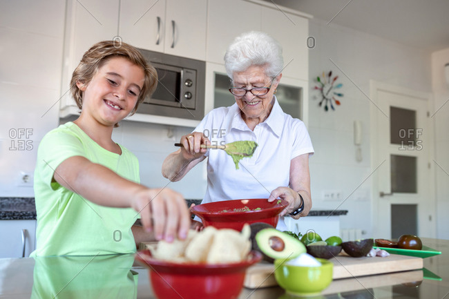 Cheerful old woman with white hair helping child while preparing guacamole together in kitchen