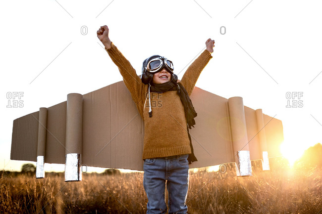 Happy kid in goggles and cardboard wings raising hands during game on field in backlit