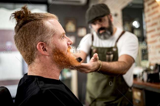 Barber with trimmer cutting beard of redhead man sitting in barbershop