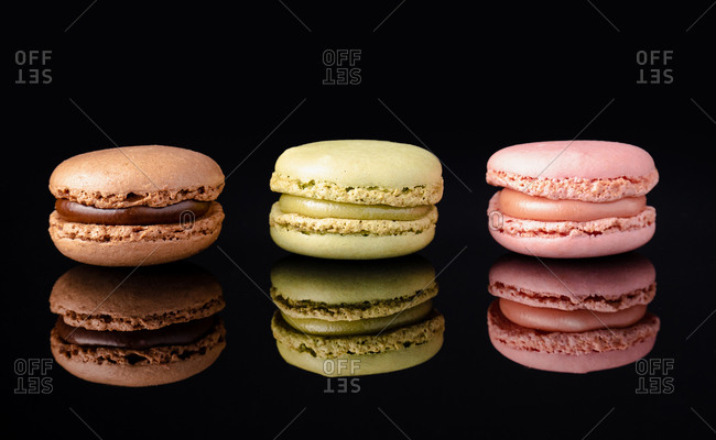 Colorful tasty macaroons stacked displayed on black background