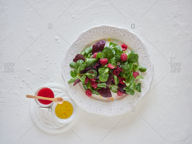 Fragrant aromatic raspberry and spinach in white plate with colorful sauce