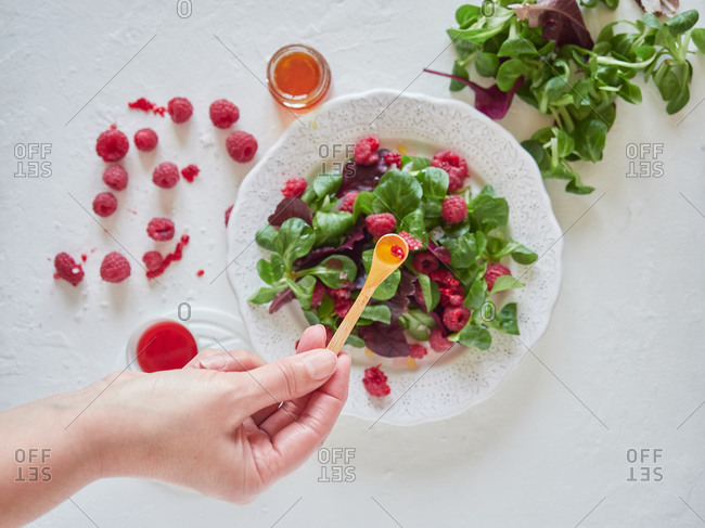 From above crop cook adding juice with spoon to tasty fresh salad with ripe raspberries and fresh spinach