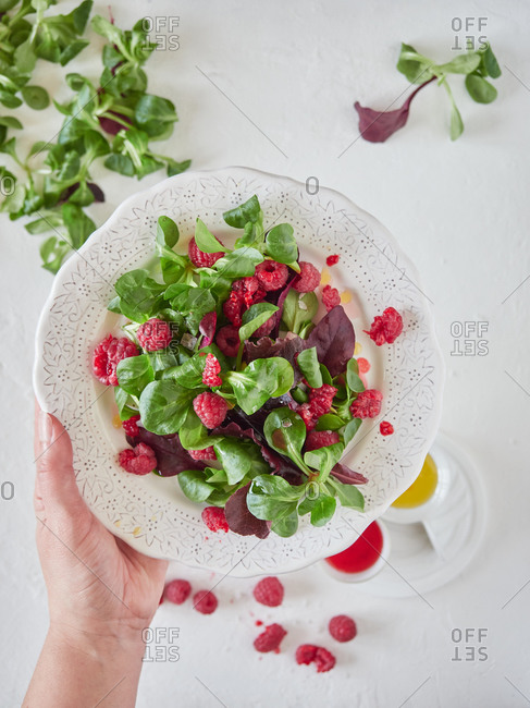 From above crop cook holding ornamental plate with tasty fresh salad with ripe raspberries and fresh spinach