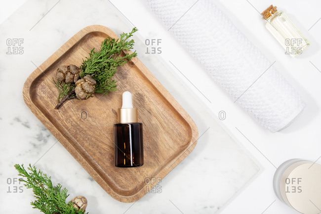Top view cypress essential oil on a marble table on wooden tray