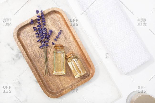 Top view lavender flower and its essential oil on a bottle at a marble table on wooden tray