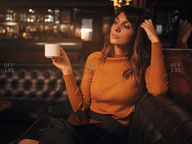 Stylish smart thoughtful woman surfing tablet comfortably sitting on black leather couch in cafe using tablet and drinking coffee in a mug