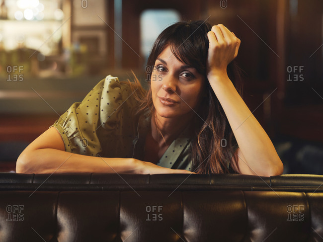 Side view of tired relaxed woman leaning on back of leather black sofa and looking at camera in cafe