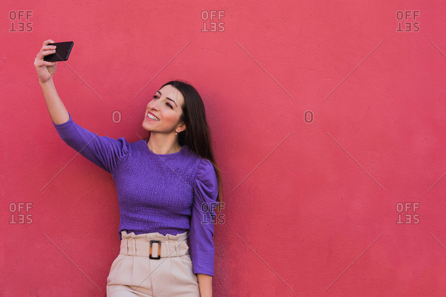 Positive young female in violet blouse and light beige pants taking a selfie on mobile phone while standing against colorful red wall background