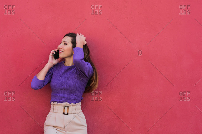Positive young female in violet blouse and light beige pants talking on mobile phone while standing against colorful red wall background