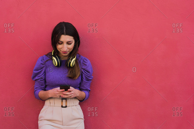 Positive young female in violet blouse and light beige pants using mobile phone while standing against colorful red wall background