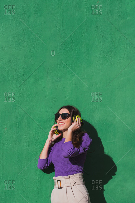 Positive young female in violet blouse and light beige pants talking on mobile phone while standing against colorful green wall background