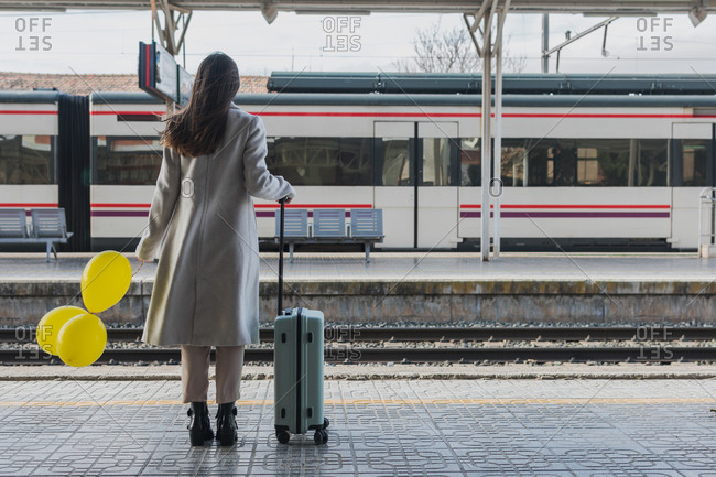 Back view of unrecognizable female traveler in stylish outfit standing with yellow balloons in hand and suitcase on platform of railway station