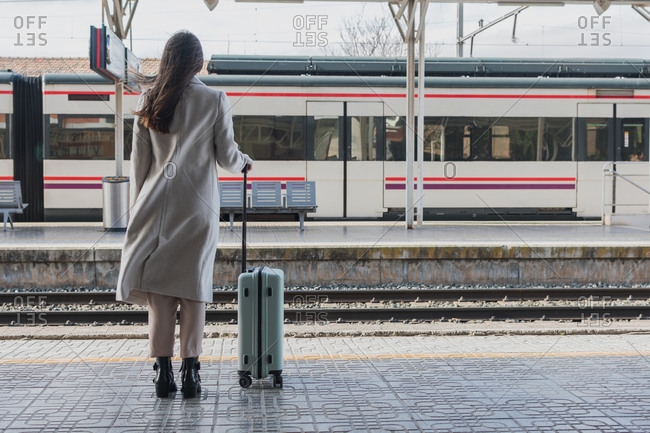 Back view of unrecognizable female traveler in stylish outfit standing with suitcase on platform of railway station