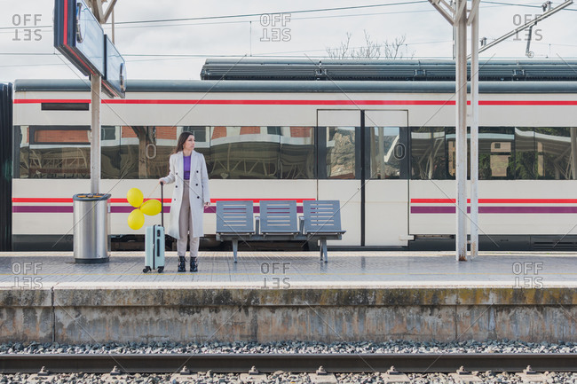 Young female traveler in stylish outfit standing with yellow balloons in hand and suitcase on platform of railway station