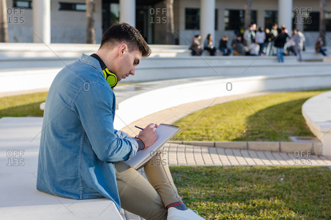 Side view of thoughtful smart male student in bright headphones studying in university square and writing in note book sitting on fence with crossed leg