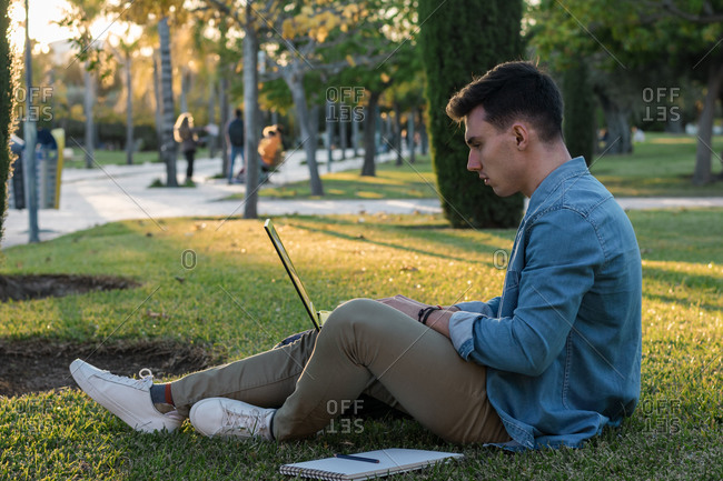 Smart concentrated man with backpack studying at laptop sitting in park grass with crossed legs in sunny day