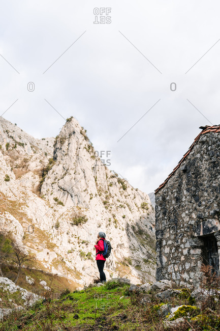 Side view of active hiker in red jacket with heavy backpack looking up at mountain in peaks of Europe, Asturias, Spain