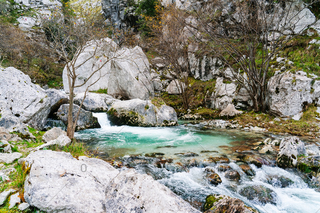 Amazing landscape of mountain waterfall and turquoise lake flowing into river in peaks of Europe, Asturias, Spain
