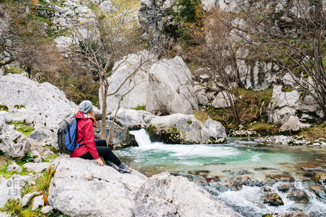 Side view of unrecognizable woman tourist in red jacket with backpack looking at mountain waterfall and turquoise lake flowing into river in peaks of Europe, Asturias, Spain