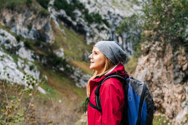 Side view of active woman hiker in red jacket with heavy backpack looking up at mountain in peaks of Europe, Asturias, Spain