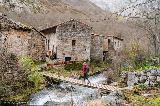 From above active woman tourist in red jacket with heavy backpack crossing way on wooden bridge in village in peaks of Europe, Asturias, Spain