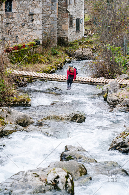 From above relaxed tourist in red jacket with backpack sitting and dangling legs on wooden bridge in village in peaks of Europe, Asturias, Spain