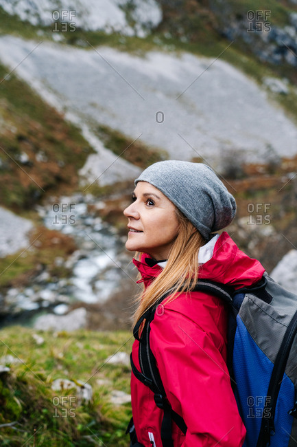 Side view of active woman hiker in red jacket with heavy backpack looking away while walking in mountain in peaks of Europe, Asturias, Spain
