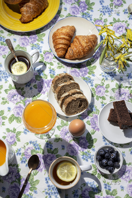 From above top view of homemade full brunch breakfast in sunlight with cooked eggs, blueberries, sponge cake, croissants, toast, tea, coffee and orange juice