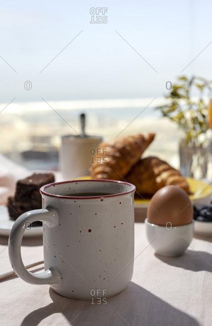 Homemade full brunch breakfast in sunlight with cooked eggs, blueberries, sponge cake, croissants, toast, tea, coffee and orange juice