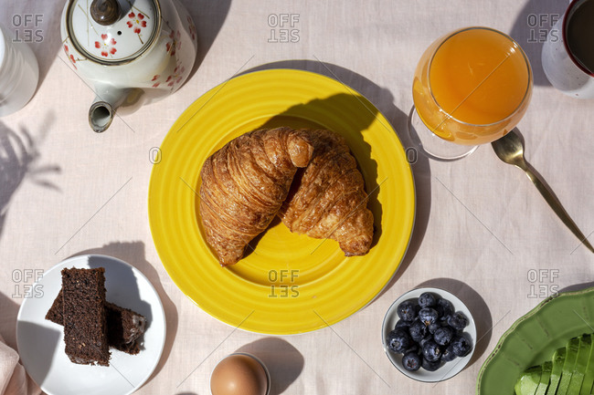 From above top view of homemade full brunch breakfast in sunlight with croissants, strawberries, tea or coffee and orange juice