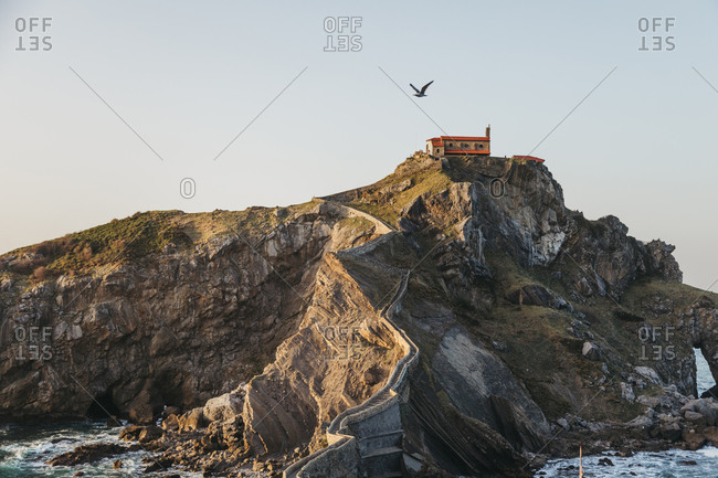 Paving stone way leading along stone bridge and ridge of rocky hill to lonely country house on island Gaztelugatxe surrounded by tranquil sea water with white foam waves