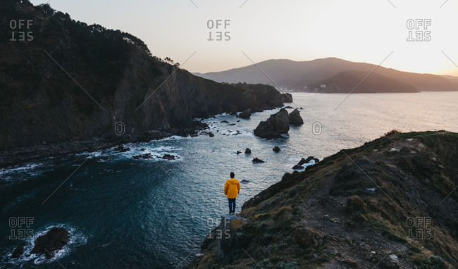 From above back view of person in vibrant yellow jacket standing on edge of cliff and enjoying amazing scenery of rocky sea coast during sunset in Spain