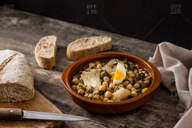 Chickpea stew with spinach and cod fish or vigil potaje on wooden table