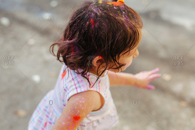 Unrecognizable cute little girl covered in dirty paint during paint festival on city street