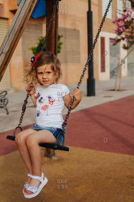 Full length little girl sitting on swing and looking at camera while resting on playground on sunny summer day
