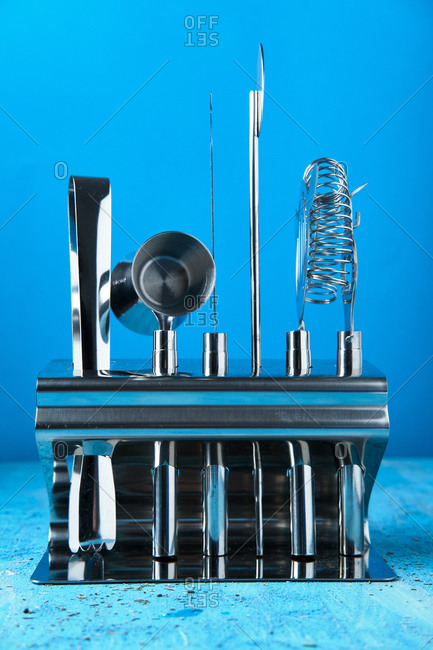 Modern stainless steel set of arranged barman equipment in stand on blue table