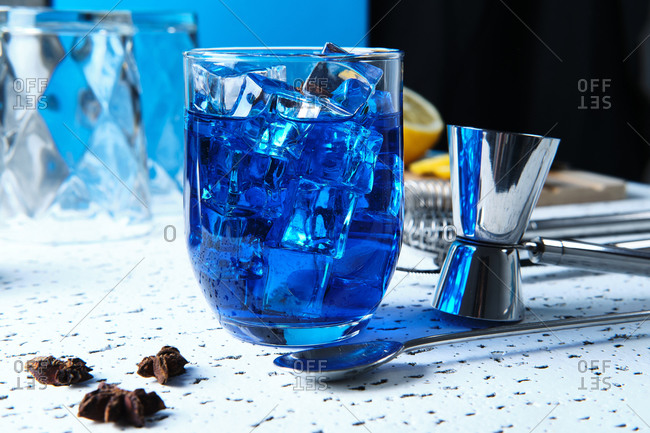 Tasty fresh blue cocktail with ice cubes and barmen tools on table